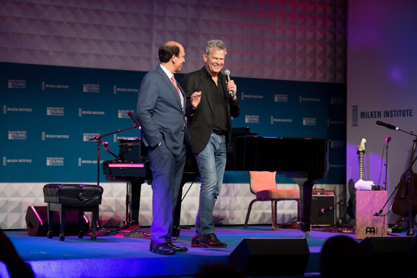 Michael Milken, left, and David Foster appear onstage together during the Late Night session at the