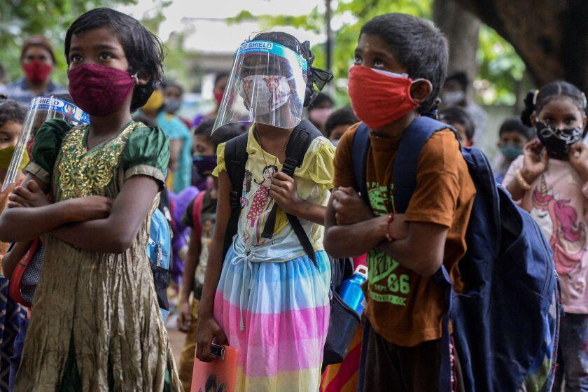 کودکان رنگارنگ لباس ماسک و کوله پشتی می پوشند