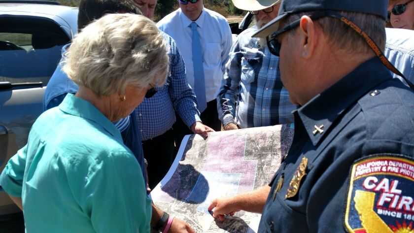 County Supervisor Dianne Jacob examines a map during a tour of an 84-acre piece of land just off sta