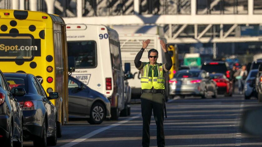 A Los Angeles airport police officer directs traffic at Los Angeles International Airport on Nov. 22, the day before Thanksgiving. The airport ranked in the middle in parking expenses among major U.S. airports, according to a new study.
