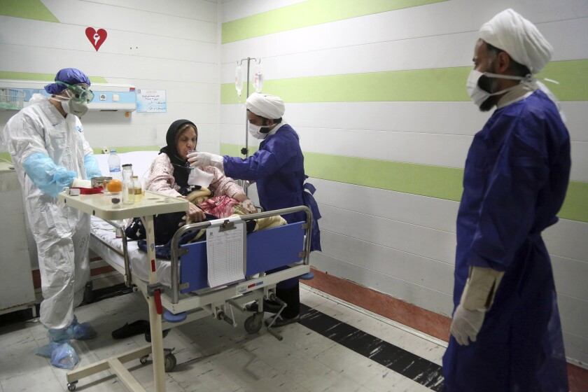 FILE — In this Saturday, March 7, 2020 file photo, a cleric, right, assists a medic treating a patient infected with the new coronavirus, at a hospital in Qom, about 80 miles (125 kilometers) south of the capital Tehran, Iran. Nine out of 10 cases of the virus in the Middle East come from the Islamic Republic. Fears remain that Iran may be underreporting its cases. Days of denials gave the virus time to spread as the country marked the 41st anniversary of its 1979 Islamic Revolution with mass demonstrations. For most people, the new coronavirus causes only mild or moderate symptoms. For some it can cause more severe illness. (Mohammad Ali Marizad/Rasa News Agency via AP, File)