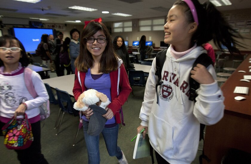 Lincoln Middle School student Dulce Lerma walks with Chinese exchange students Wu Xin Yi (left) and Liau Wen Lie at the school Tuesday. Bill Wechter • U-T