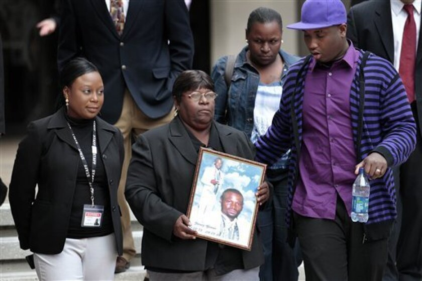 Edna Glover, second left, mother of Henry Glover, leaves Federal Court holding his photo, after the sentencing of two former New Orleans police oficers in his shooting death and burning of his body in New Orleans, Thursday, March 31, 2011. Former officer David Warren was sentenced to more than 25 y
