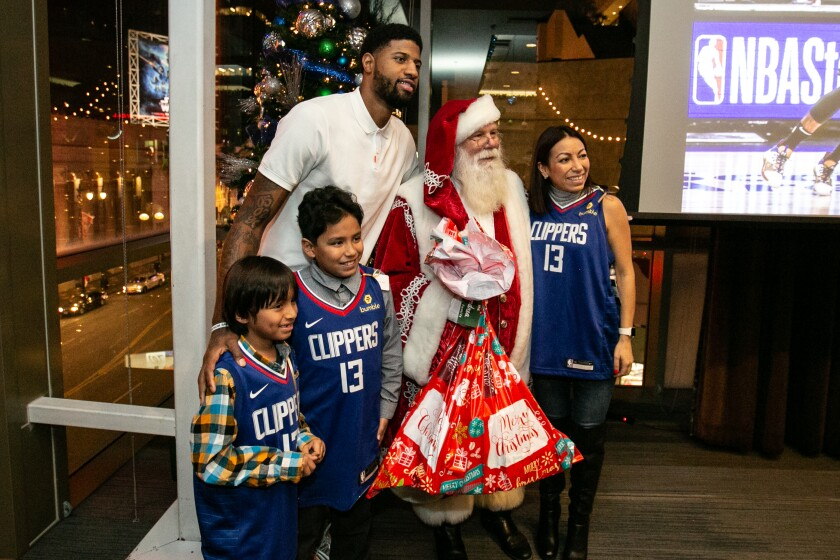 Paul George and Santa take a photo with the Paez family.