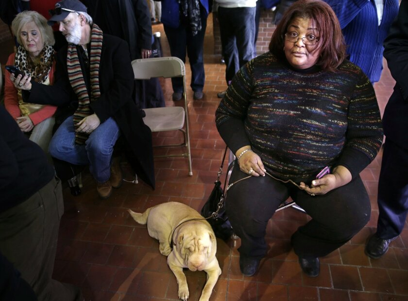 In this Feb. 16, 2015 file photo, a Chinese shar-pei named Deniro sits with his owner, Maria Johnson, right, before competing at the Westminster Kennel Club show in New York. Johnson, of Newark, N.J., is among the relatively small ranks city dwellers who work to breed show-quality dogs in their hom