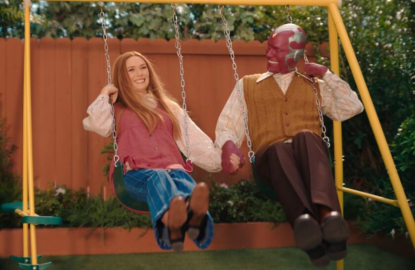 """Elizabeth Olsen and Paul Bettany swing on a swing set in a yard in a scene from """"WandaVision."""""""