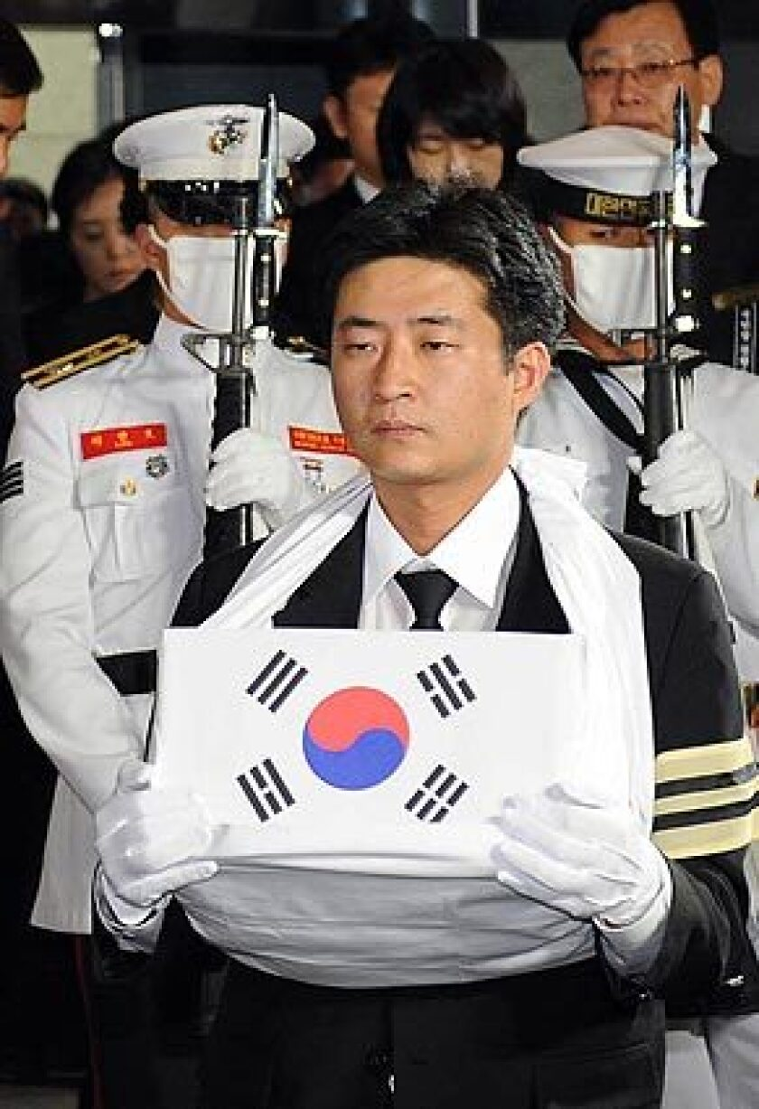 Roh Gun-ho, a son of former South Korean President Roh Moo-hyun, carries his father's ashes at a crematorium in Seoul.