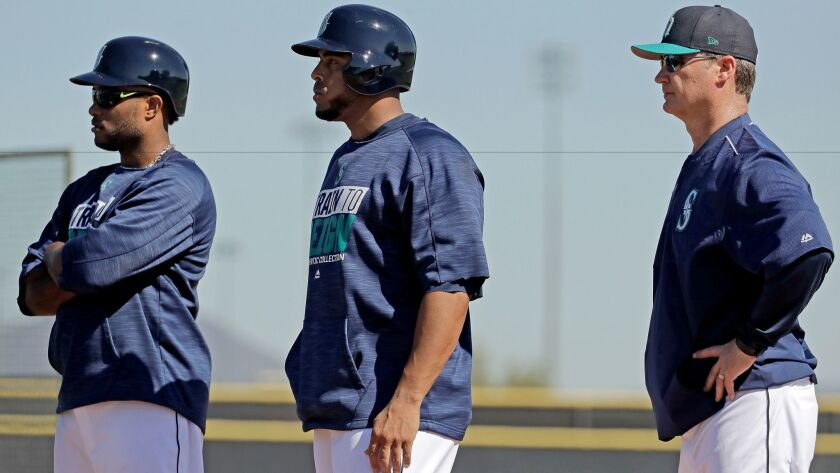 Mariners players Robinson Cano, left, Nelson Cruz, center, and manager Scott Servais watch batting practice during spring training baseball practice Tuesday, Feb. 21, 2017, in Peoria, Ariz.