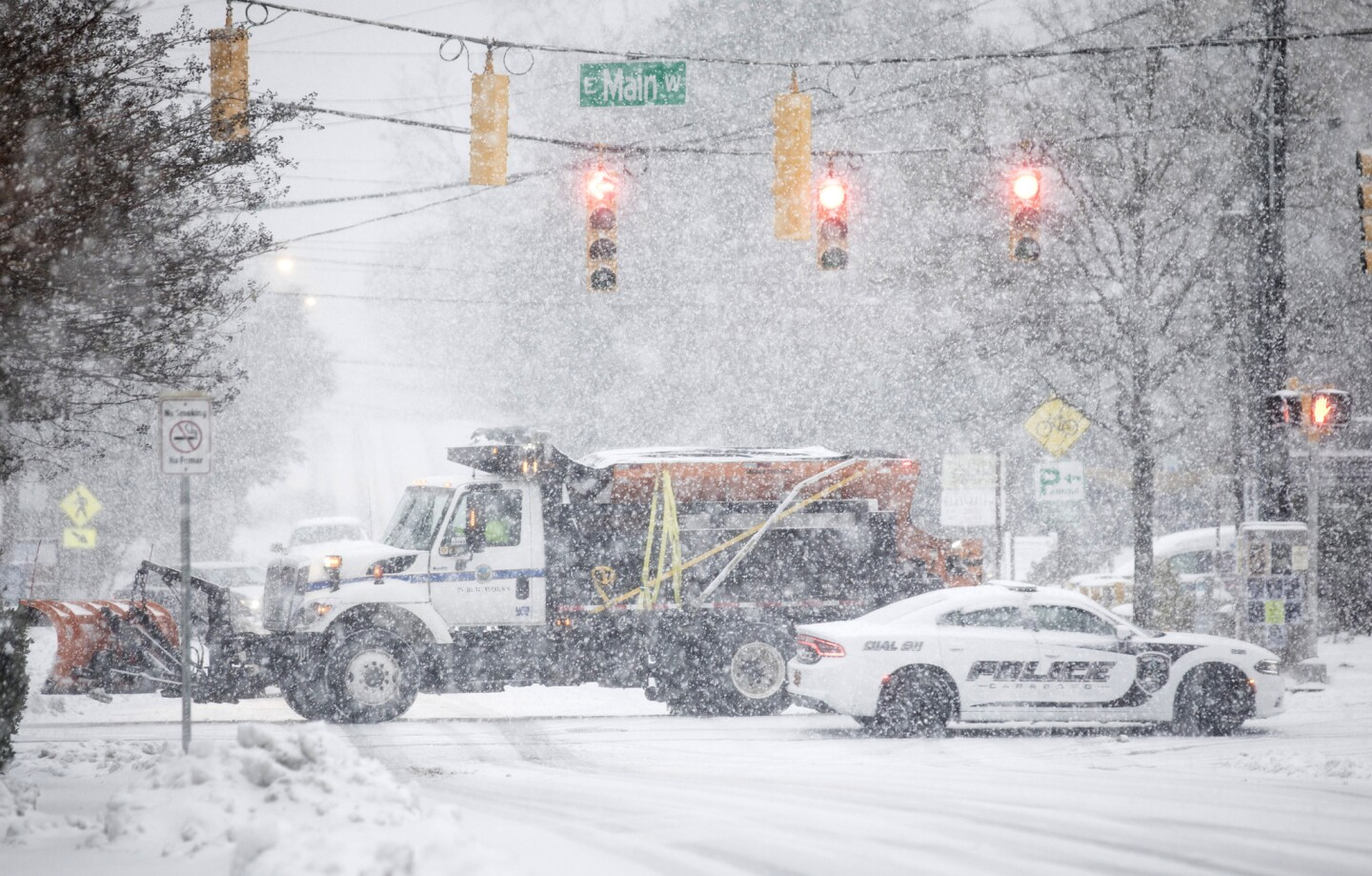A snow plow and a police vehicle pass each other in Carrboro, N.C., on Monday. A lingering storm kept dumping immobilizing snow, sleet and freezing rain across five Southern states, leaving dangerously icy roads and hundreds of thousands of people without electricity.