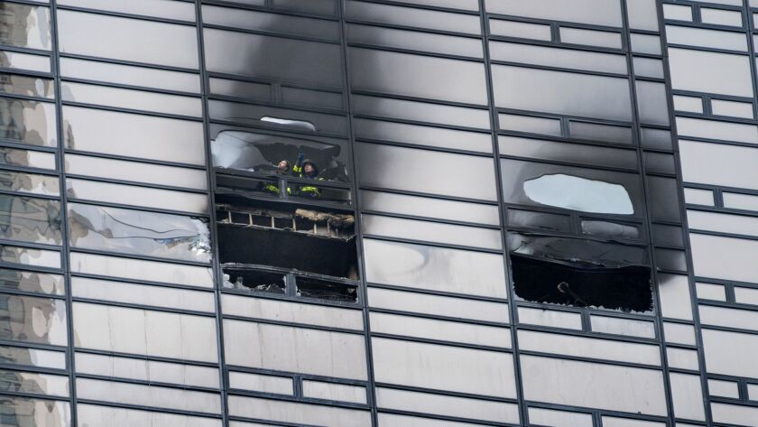 Firefighters look out from the window of a damaged apartment in Trump Tower on Saturday,