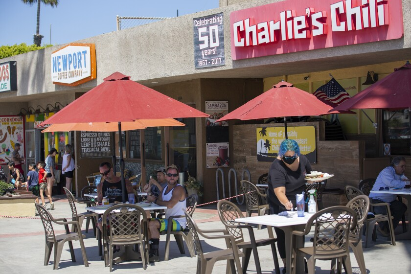 Patrons eat lunch at Charlie's Chili near the Newport Beach Pier on May 27.