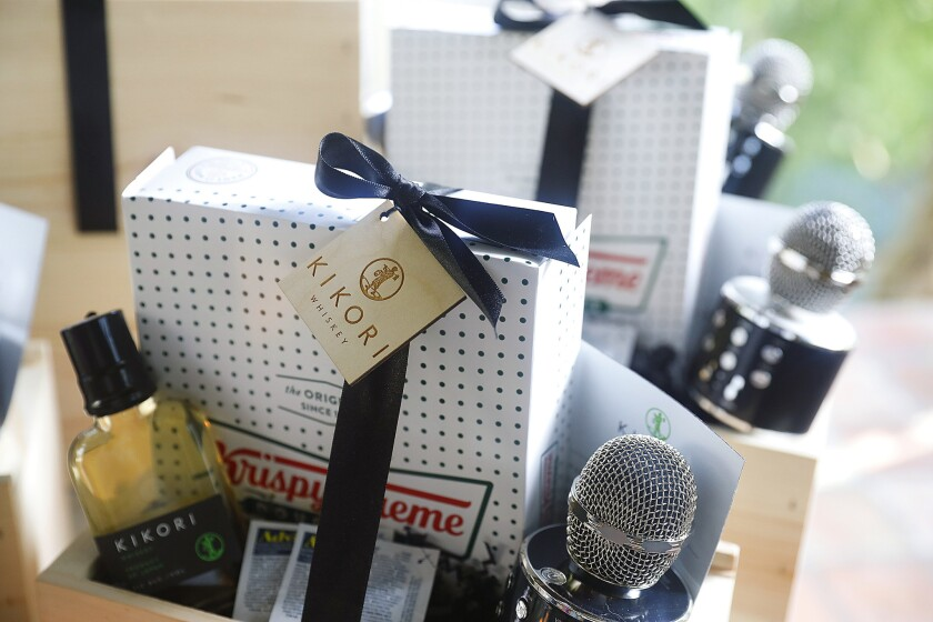 Parting gift boxes of Krispy Kreme donuts, packets of Advil, a bottle of Kikori whiskey, a handheld karaoke mic, and a karaoke song list on a magnet, at the home of Ann Soh Woods.