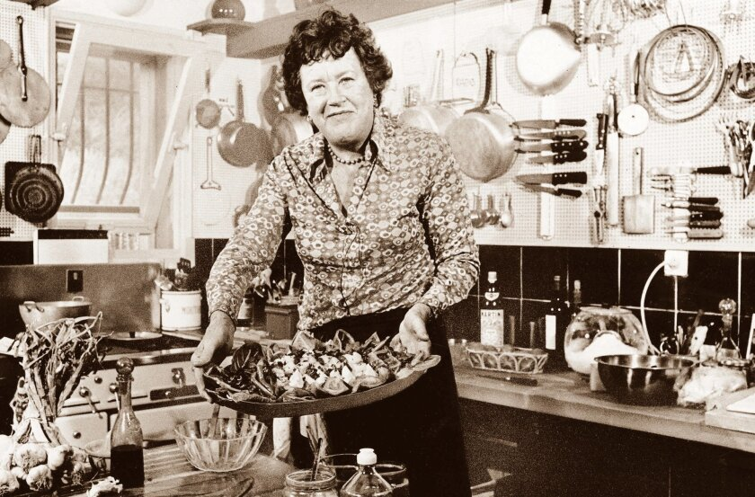 In this 1978 photo, Julia Child shows off a salade nicoise she prepared in the kitchen of her vacation home in southern France.