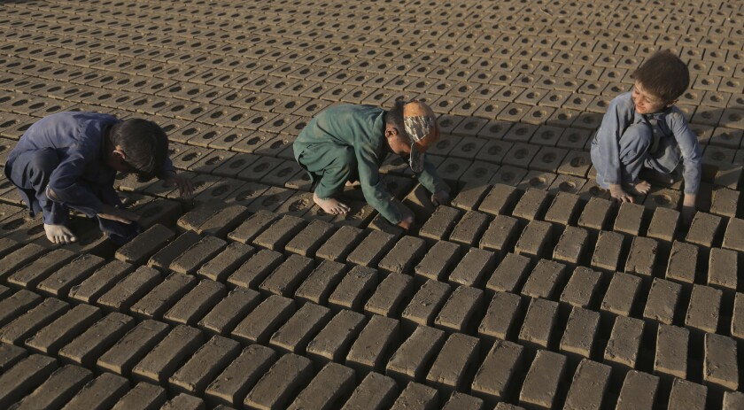 Afghan children help their father's work at a local brick factory on the outskirts of Kabul, Afghanistan, Wednesday, Aug. 1, 2018.
