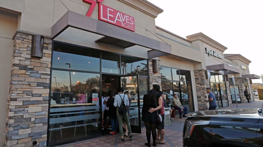 A couple waits outside in line at 7 Leaves Cafe in Garden Grove.