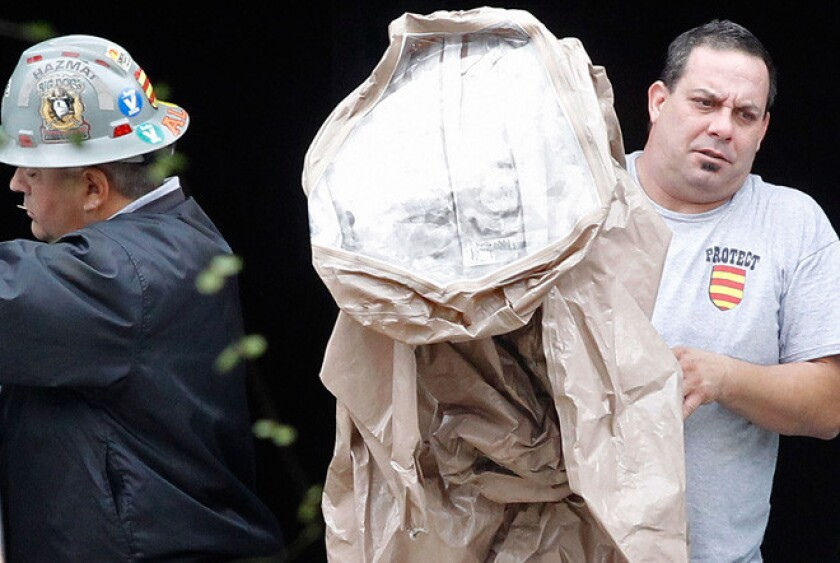 A hazardous materials worker prepares to put on protective gear outside the Dallas apartment where a nurse diagnosed with the Ebola virus resides.