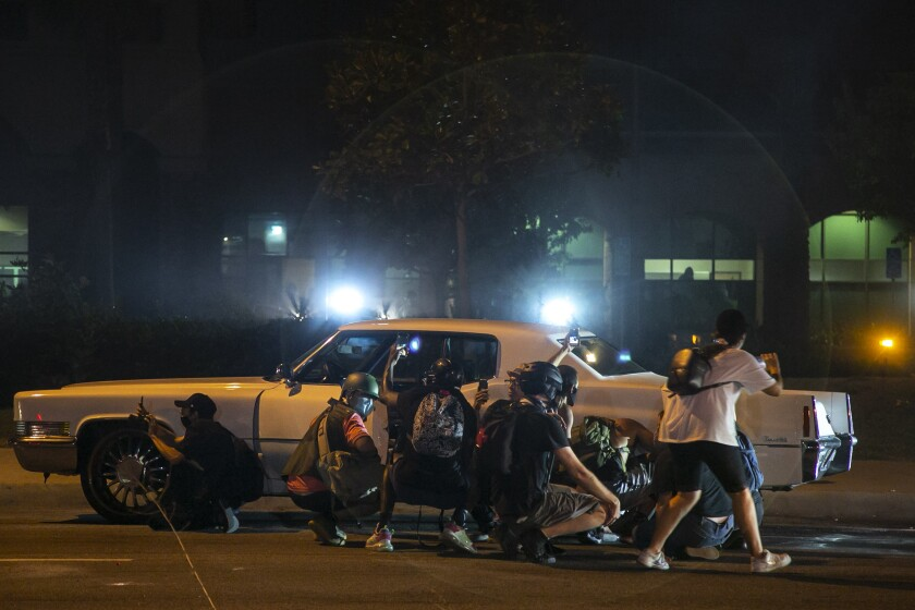 People use a car for cover Saturday after deputies fired nonlethal projectiles during a protest over Dijon Kizzee's killing.