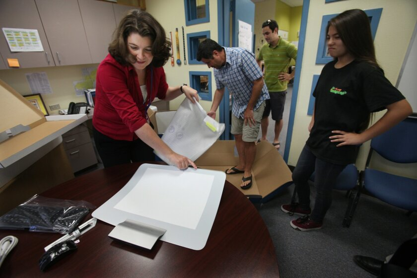 Lee Fleming, new principal at Bonsall High School, was excited to receive new computers delivered to her offices on Thursday.  Fleming, left, with world studies teacher Danny Costa, lift a new Sprout monitor from its box, while student Brieanna Elzenga, 14, watches.