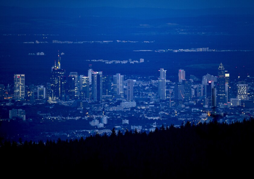 The buildings of the banking district are seen from above after sunset in Frankfurt, Germany, Tuesday, Aug. 25, 2020. (AP Photo/Michael Probst)