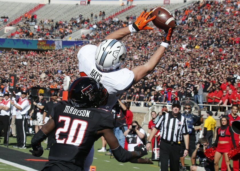Oklahoma State wide receiver Austin Hays, top, catches a pass for a touchdown in front of Texas Tech defender Tevin Madison (20) in the first quarter of an NCAA college football game in Lubbock, Texas, Saturday, Oct. 31, 2015. (AP Photo/Sue Ogrocki)