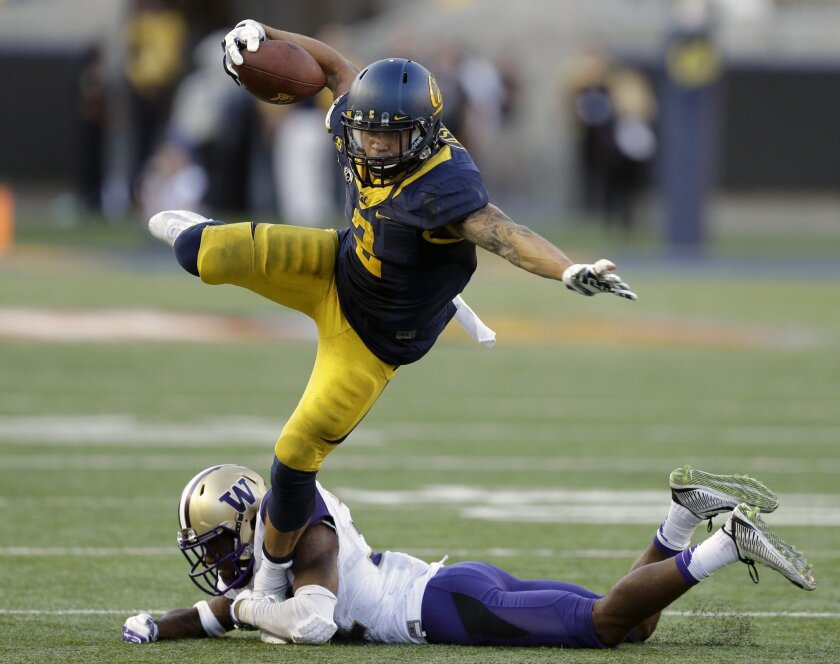 California's Daniel Lasco (2) tries to evade the grasp of Washington's Budda Baker during the second half of an NCAA college football game Saturday, Oct. 11, 2014, in Berkeley, Calif. (AP Photo/Ben Margot)