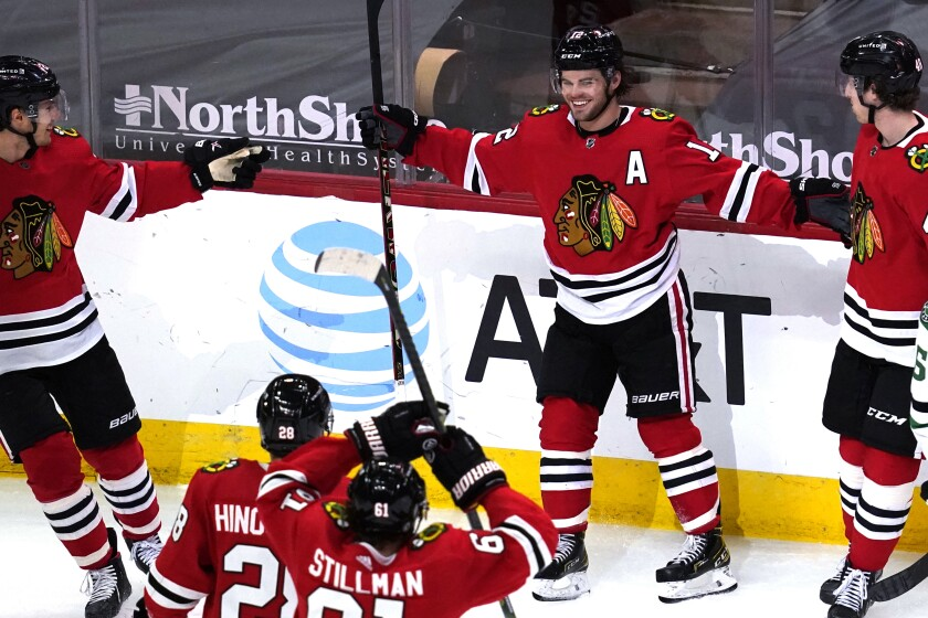 Chicago Blackhawks left wing Alex DeBrincat, second from right, smiles after scoring his second goal against the Dallas Stars, during the third period of an NHL hockey game in Chicago, Sunday, May 9, 2021. (AP Photo/Nam Y. Huh)