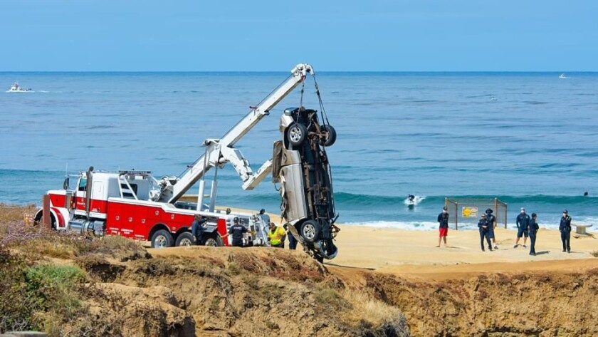 Crews recover the wreckage of a pickup that crashed over the edge of Sunset Cliffs
