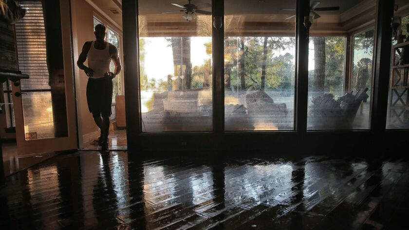 Charles Lewis walks into his living room next to windows that show how high the water came.