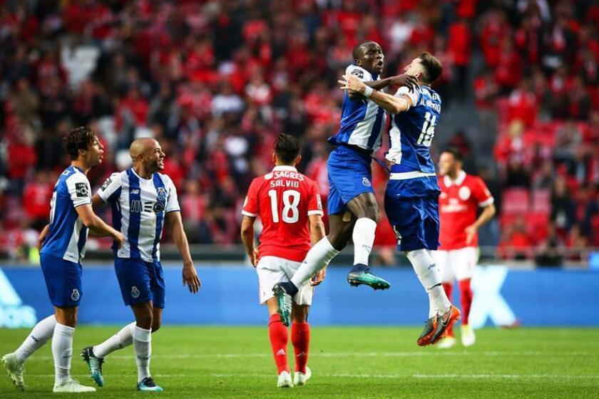 FC Porto's Hector Herrera (R) celebrates with his teammate Vincent Aboubakar (C) after scoring the winning goal during the Portuguese First League soccer match between Benfica Lisbon and FC Porto at Luz stadium in Lisbon, Portugal. EFE/EPA