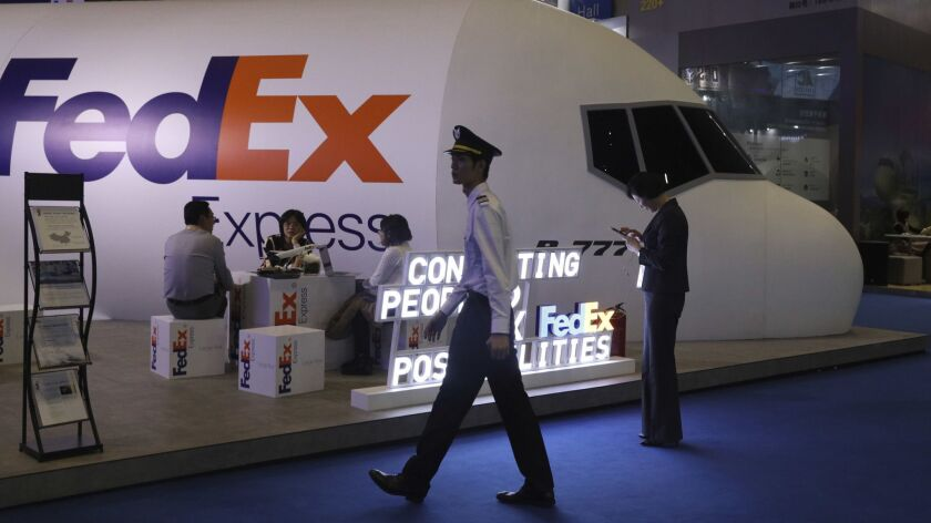 FILE - In this Nov. 5, 2018, file photo, a man dressed as a pilot walks past the FedEx booth during