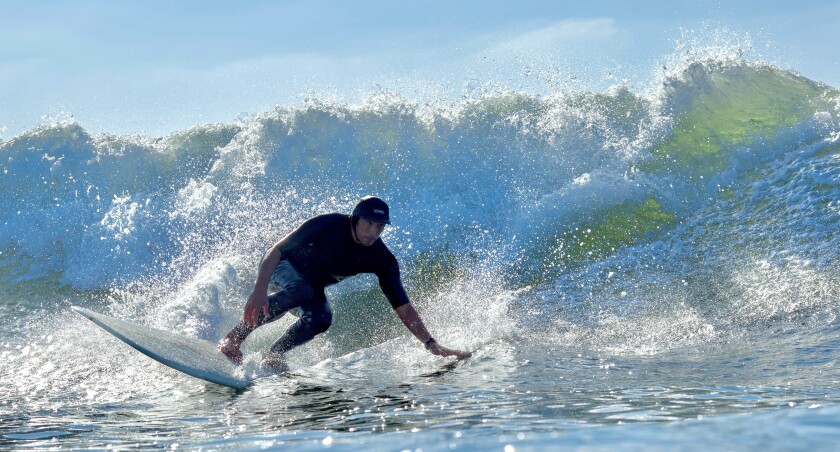Point Loma Nazarene professor Ben Cater surfs at Sunset Cliffs.