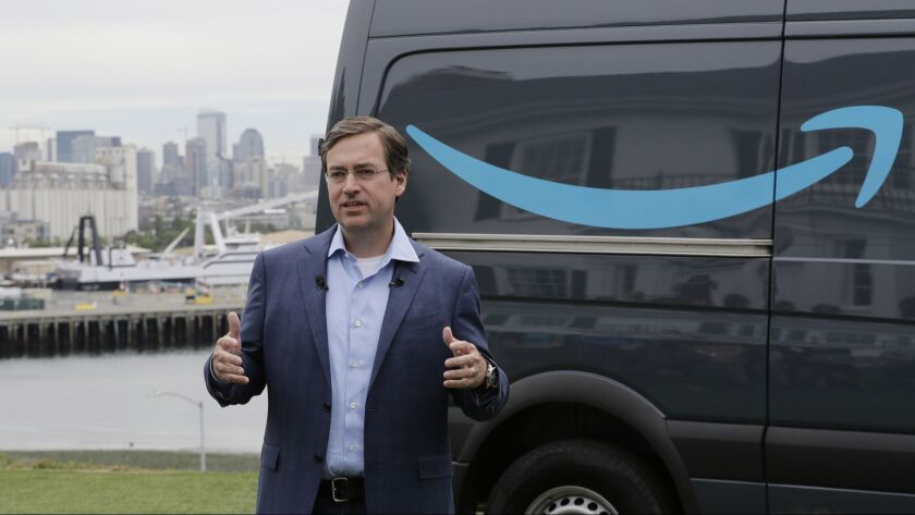 Dave Clark, an Amazon executive, talks in Seattle on Wednesday about a new program for entrepreneurs to use Amazon Prime-branded vans and get support from the company as they form businesses to deliver company packages.