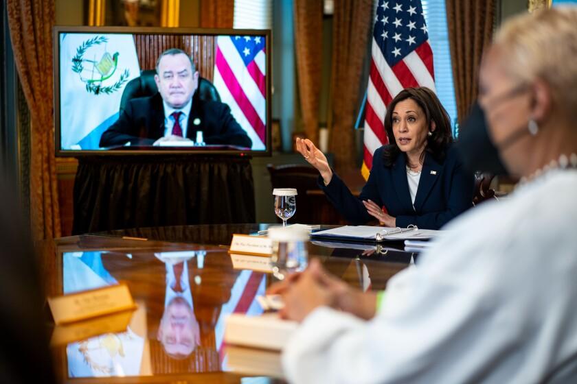 Vice President Kamala Harris speaks to Guatemalan President Alejandro Giammattei, who appears onscreen.