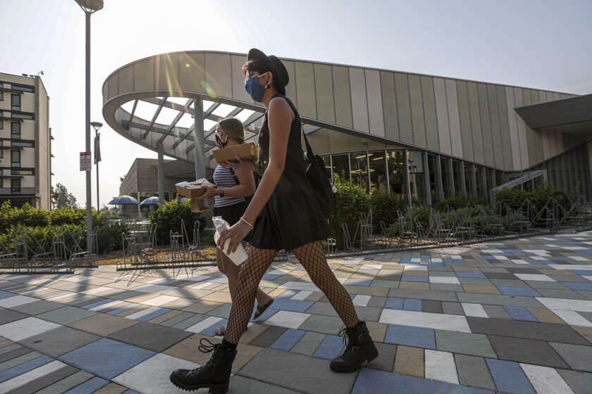Two women wearing masks walk on a college campus while carrying takeout boxes