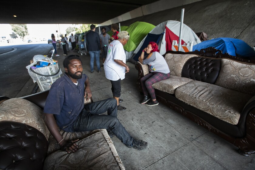 Dennis Karimi, 30, sits on a couch that also serves as his bed at the homeless encampment in Pacoima.