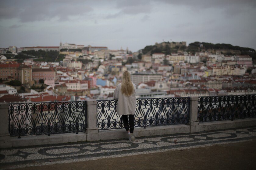 A woman stands at a viewpoint overlooking Lisbon's old center, a site popular with tourists and now mostly deserted, Monday, Feb. 8, 2021. Hopes are rising in Portugal that the worst of a devastating pandemic surge might be over, as the number of COVID-19 deaths reported Monday was the lowest in three weeks. Still, the national lockdown could remain in place through mid-March, officials have said. (AP Photo/Armando Franca)