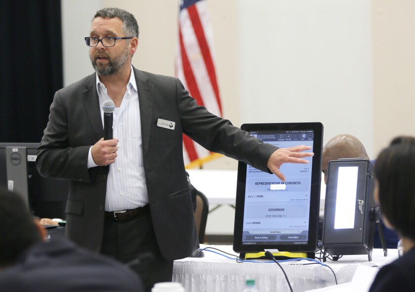 FILE - In this Aug. 30, 2018 file photo, Eric Coomer from Dominion Voting demonstrates his company's touch screen tablet that includes a paper audit trail at the second meeting of Secretary of State Brian Kemp's Secure, Accessible & Fair Elections Commission in Grovetown, Ga. Attorneys for President Donald Trump's re-election campaign, its onetime attorney Rudy Giuliani and conservative media figures asked a judge Wednesday, Oct. 13, 2021, to dismiss a defamation lawsuit by Coomer, a former employee of Dominion Voting Systems, who argues he lost his job after being named in false charges as trying to rig the 2020 election. (Bob Andres/Atlanta Journal-Constitution via AP, File)