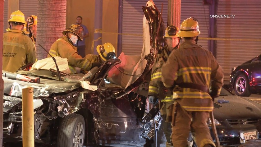 Firefighters stand near a crushed black sedan.
