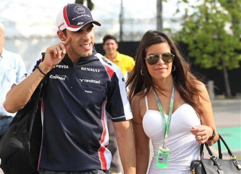 Williams Formula One driver Pastor Maldonado of Venezuela walks with his girlfriend Gabriella Tarkany as he arrives for the third practice session for the Singapore Formula One Grand Prix on the Marina Bay City Circuit in Singapore, Saturday, Sept. 22, 2012. (AP Photo/Wong Maye-E)
