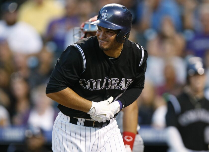 Colorado Rockies' Nolan Arenado, front, reacts after getting hit in the hand by Cincinnati Reds starting pitcher Johnny Cueto in the seventh inning of a baseball game Saturday, July 25, 2015, in Denver. Cincinnati won 5-2. (AP Photo/David Zalubowski)