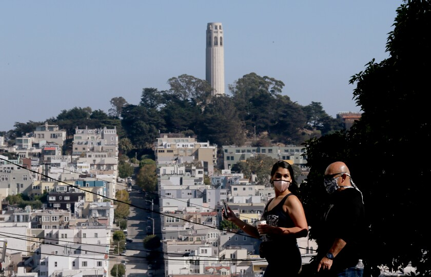 Housing stacks a hillside that's topped by Coit Tower as pedestrians walk by wearing masks.