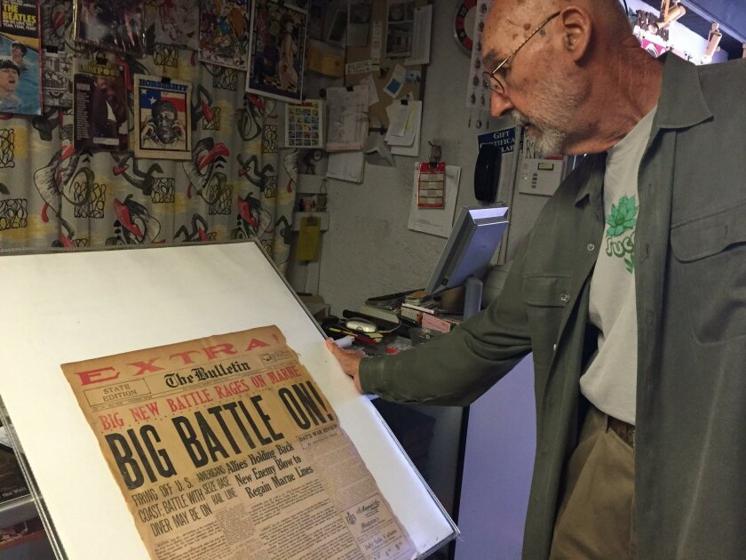 Jerry Waddle, owner of Ducky Waddle's Emporium in Leucadia, with a vintage newspaper front page from World War I. The emporium is closing its doors.