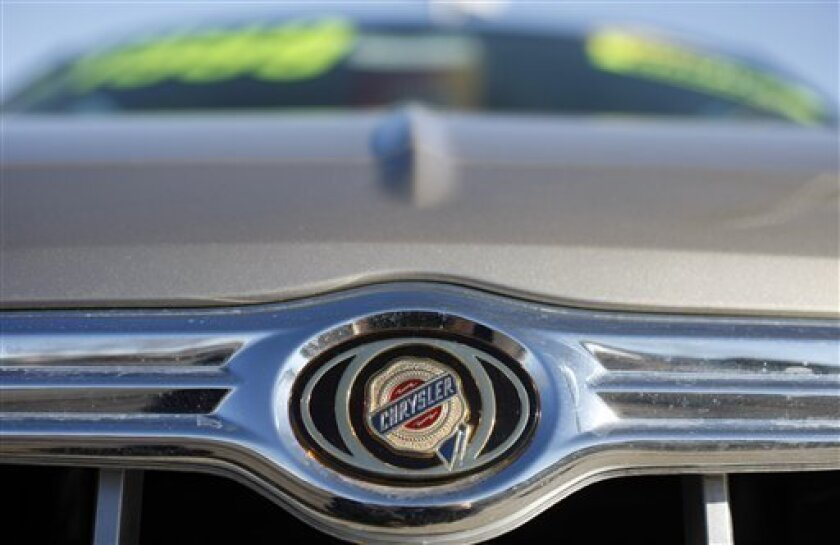 The company logo shines off the top of a grille on an unsold 2008 300 sedan at a Chrysler-Jeep dealership in Golden, Colo., on Sunday, Feb. 1, 2009. A union official says Chrysler LLC is offering another round of buyout and early retirement packages to hourly workers in an effort to replace them with new hires who would earn less money. (AP Photo/David Zalubowski)