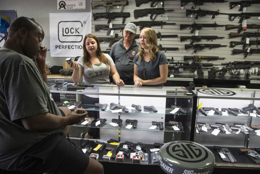 Store Managers Jamie Taflinger,left and Kendyll Murray show customer Cornell Hall ammo at the Get Loaded gun store in Grand Terrace, which has seen a surge in gun sales.