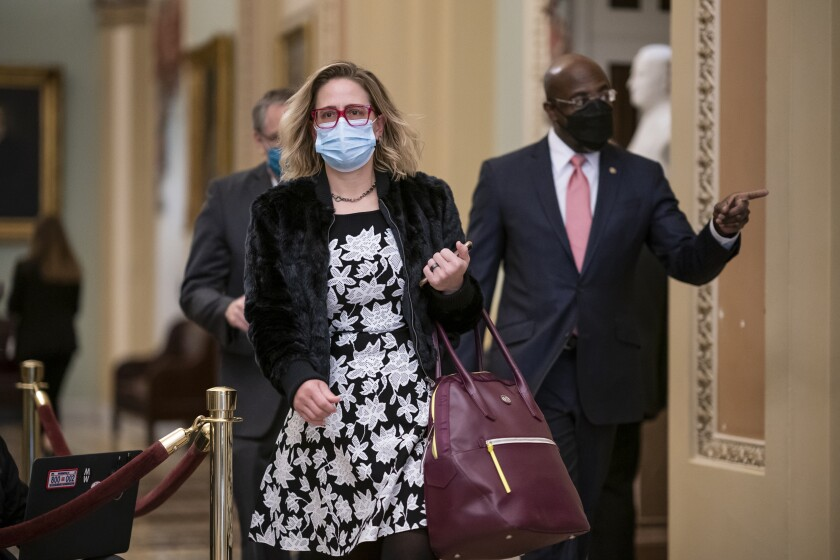 Sen. Kyrsten Sinema, masked and walking with Sen. Raphael Warnock in the Capitol.