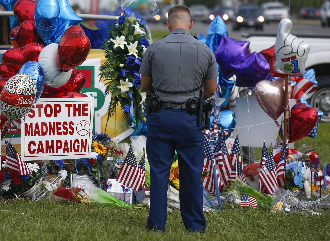 Louisiana police officer PJ Freeman stops to pay his respects at a roadside memorial for the three officers slain in Baton Rouge.
