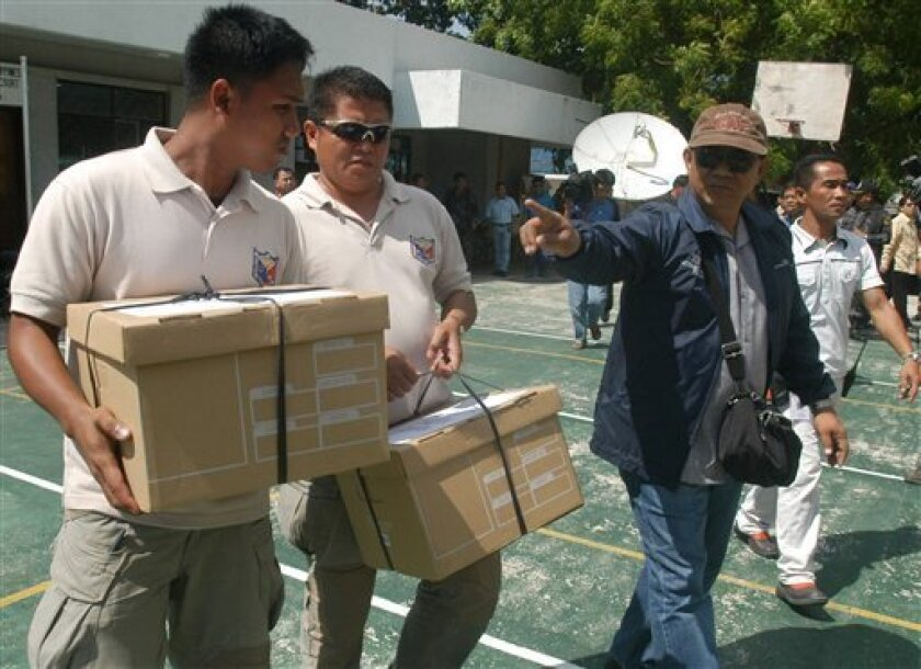 Police officers in civilian clothes carry two boxes of legal documents to the Hall of Justice building in Cotabato City, southern Philippines, on Tuesday, Dec. 1, 2009. Prosecutors initially filed 25 murder charges against Andal Ampatuan Jr. whom witnesses said led gunmen including police officers who blocked his rival's election caravan moments before the massacre of 57 people, nearly half of them journalists in Ampatuan town, southern Philippines. (AP Photo/Froilan Gallardo)