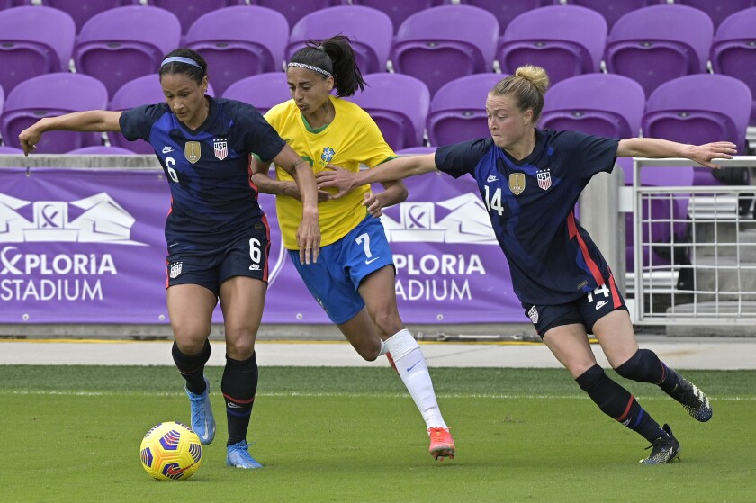 Brazil midfielder Andressa on the field with Americans Lynn Williams and Emily Sonnett.