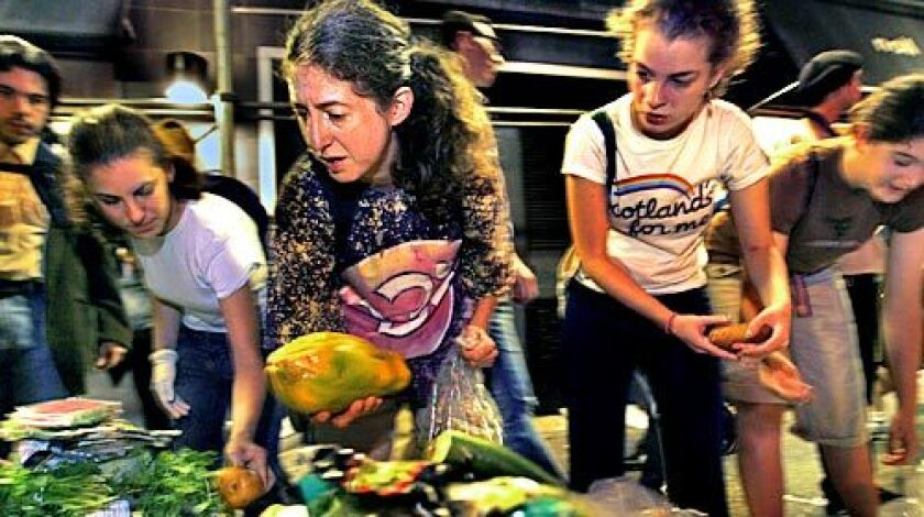 "Janet Kalish, center, with a papaya she collected during a New York City trash tour for people interested in becoming freegans -- anti-consumerists who, in the words of one advocate, are ""opting out of capitalism in any way that we can."""