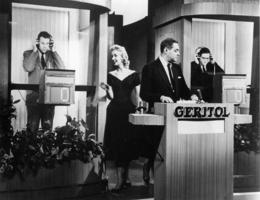 "A scene from the 1950s TV game show ""Twenty One,"" with contestant Charles Van Doren, left. Host Jack Berry is in the middle and the other contestant is Herbert Stempel, right."